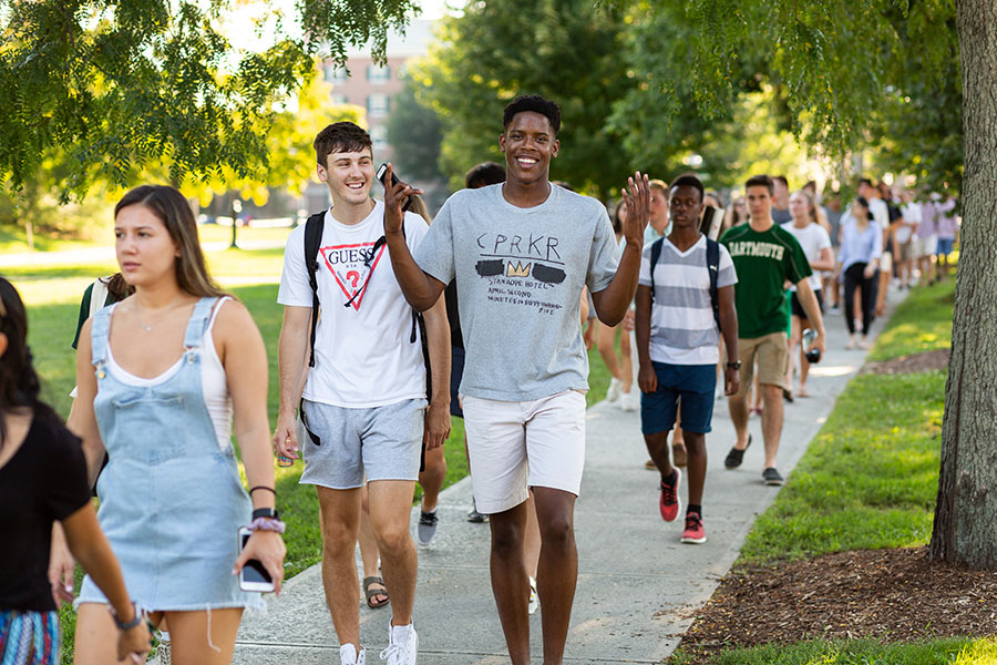 Students walk along a sidewalk in Hanover