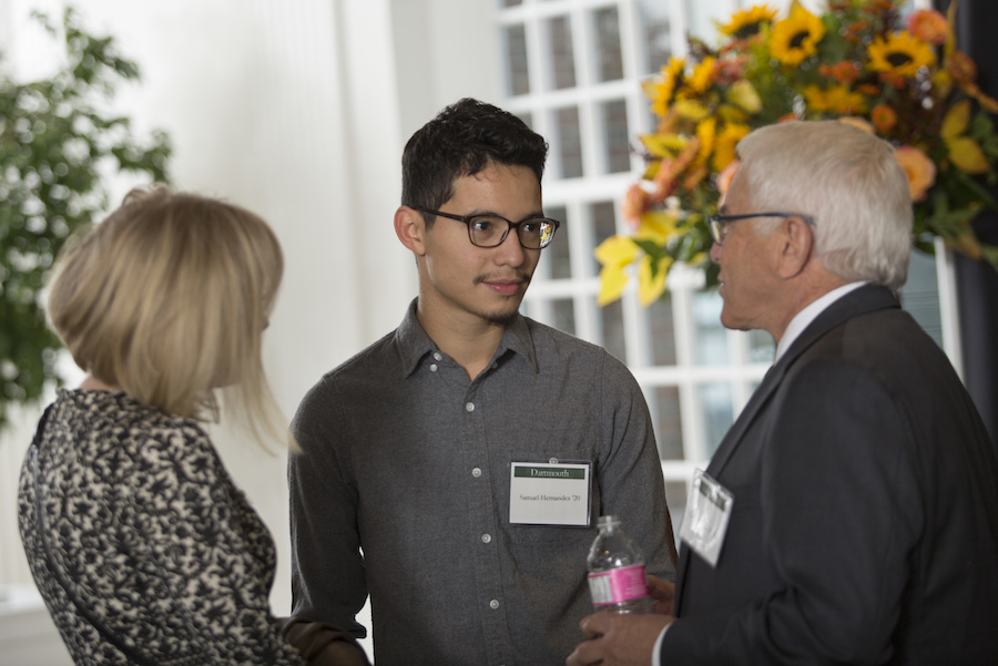 A young man chats with an older couple.