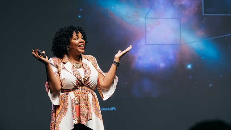 A woman gestures in front of a map of the cosmos